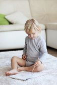 Toddler drawing pictures sitting on a carpet at home