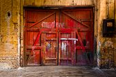 stock photo of warehouse  - Old Red Wood Gate In Industrial Interior - JPG
