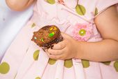 Midsection of birthday girl holding cupcake at home