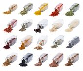 Herbs and spices spilling from spice jars isolated on white background