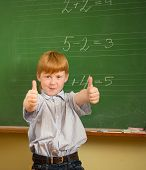 Little funny redhead schoolboy near blackboard with thumbs up