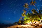 Bar on the beach among palm trees and sky with star trails. Koh Chang, Thailand