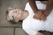 stock photo of cpr  - A senior lade with cardiac arrest or stroke receiving cpr - JPG