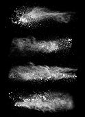 Freeze motion of white dust explosions isolated on black background