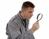 Man With Raincoat Is Looking With Magnifying Glass Over White Background