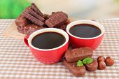 Red cups of strong coffee with chocolate bars on tablecloth on bright background
