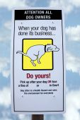 stock photo of dog poop  - sign warning about fines for dogs fouling with cloudy background - JPG