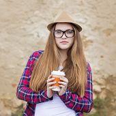 stock photo of girl walking away  - Teenage hipster girl enjoying her take away drink walking down the city street - JPG
