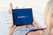 Girl Lying By The Pool And Holding Ipad With App Booking On The Screen