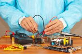 Master checks electronic board with a multimeter in service workshop