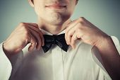 Happy Young Man Tying Abow Tie