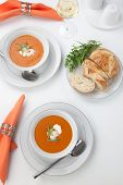 stock photo of lobster tail  - Two bowls of lobster bisque garnished with slice of lobster tail cream and fresh tarragon - JPG