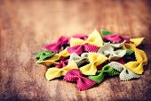 Raw Italian Pasta On Wooden Table With Copyspace For Text.  Raw Bow Tie Colourful  Pasta Macro. Ital
