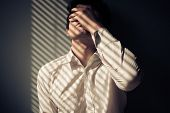 stock photo of blind man  - Young man next to a window with shadows being cast from the blinds - JPG