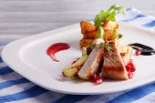 Grilled meat  with fried potato and marrow pieces and pomegranate seeds on plate, on wooden table background