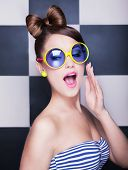 Attractive surprised young woman wearing sunglasses on checkered background, beauty and fashion conc