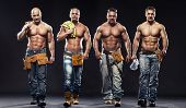 stock photo of shirtless  - Group of young handsome builder posing on dark background - JPG