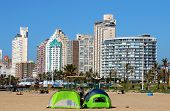 Tents Pitched 0N Beach Against City Skyline