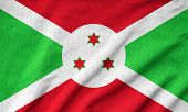 stock photo of burundi  - Ruffled Burundi Flag on wave fabric background - JPG