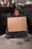 pic of beggar  - Poor beggar boy on the street with a blank stare holding cardboard sign  - JPG