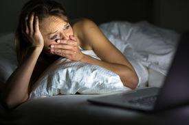 stock photo of saddening  - Pretty young woman watching something awful - JPG