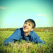 image of wallow  - Toned photo of Happy Teenager lying in the Field and looking on the Sky - JPG