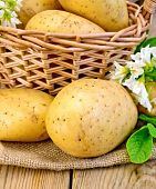 Potatoes yellow with flower and basket on wooden board