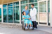 Full length of nurse and doctor looking at patient on wheelchair outside hospital building