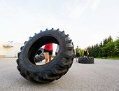 Female athlete lifting large tire outdoors