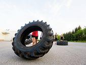 Female athlete lifting large tire outdoors