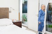 Portrait of senior woman standing by window in bedroom at nursing home