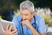 Male doctor using tablet PC while sitting at nursing home