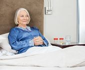 Smiling senior woman with hands clasped relaxing on bed at nursing home