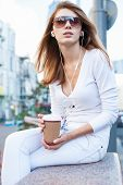 Cheerful stylish young woman drinking coffee outside on urban background