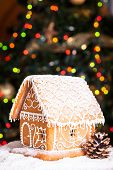 stock photo of gingerbread house  - gingerbread house over defocused lights of Chrismtas decorated fir tree - JPG