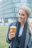 Young woman enjoying coffee on a cold day standing outdoors in a warm winter scarf holding a takeaway mug and smiling at the camera