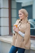 Smiling blond woman pausing for a mug of coffee standing leaning on an exterior window ledge cradling the warm drink in her hands with a smile
