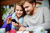Portrait of young couple using cellular phone
