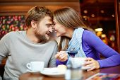 Portrait of young man and his girlfriend having date in cafe