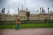 Woman stands in front of Royal Pavilion in Brighton, England