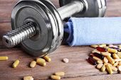 Dumbbell, towel and colorful pills, tablets, on wooden background
