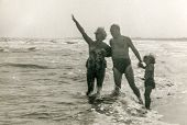 Vintage photo of parents enjoying beach with little daughter, fifties