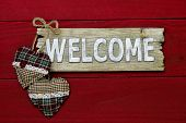 Wood welcome sign with plaid country Christmas hearts hanging on dark red wood background
