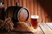pic of fermentation  - Beer barrel with beer glass on table on wooden background - JPG