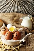 Eggs and fresh milk in glass jug, on wooden background. Organic products concept