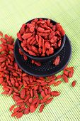 Goji berries in black cup and saucer on bamboo mat background