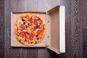 Italian pizza with ham, tomatoes, and olives in box, on gray table background