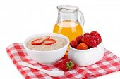 Tasty oatmeal with berries and juice isolated on white