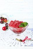 Closeup of cherry granita in glass bowl, on color wooden background
