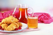 Breakfast with apple juice, jam and fresh croissants on wooden table, on bright background